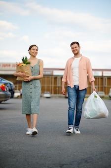 Молодая пара с сумками на парковке супермаркета