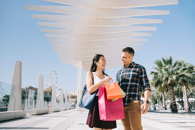 Young couple with bags walking outside