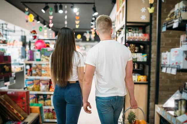 Молодая пара с корзиной в продуктовом супермаркете, вид сзади. покупатели продуктовые