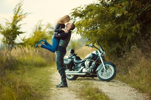 道路上の美しいバイクと若いカップル。