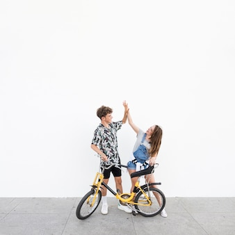 Young couple with bicycle giving high five to each other
