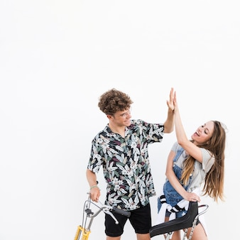 Young couple with bicycle giving high five on white backdrop