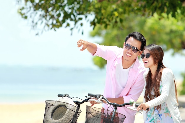 ビーチで自転車と若いカップル