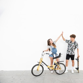Young couple with bicycle and skateboard giving high five