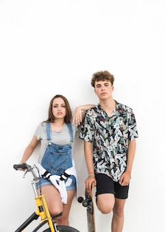 Young couple with bicycle and skateboard standing on white background
