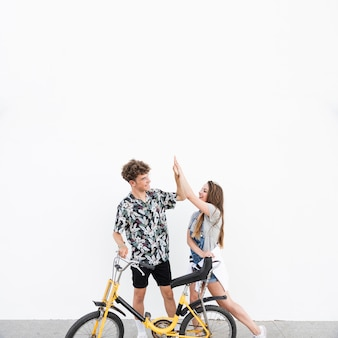 Young couple with bicycle standing on sidewalk giving high five