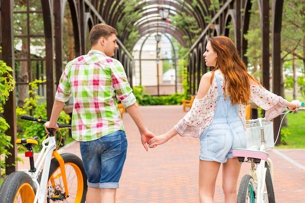 자전거를 들고 손을 잡고 공원의 아치형 통로에서 자유 시간을 보내는 젊은 부부