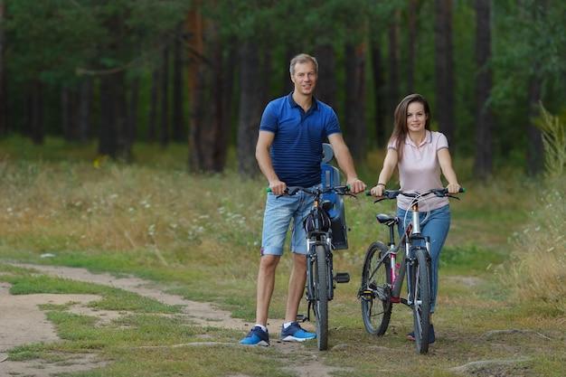 夏の日にサイクリング、公園で自転車と若いカップル。スポーツ、アクティブで健康的なライフスタイルのコンセプト。コピースペース