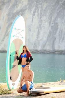 Молодая пара с досками для серфинга у реки