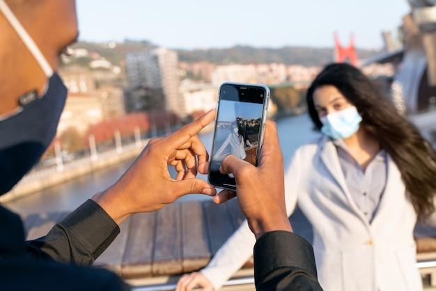 Молодая пара с парнем в афро-стиле на улице фотографируется на свой мобильный телефон, потому что они посещают бильбао с маской для лица из-за пандемии коронавируса covid-19 в 2020 году