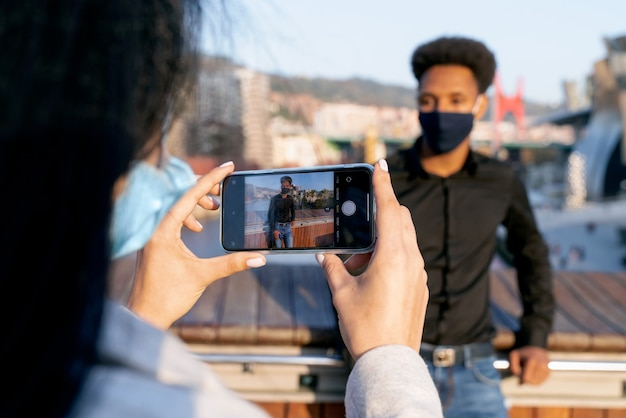 Young couple with boy afro style hair in the street taking a picture with their mobile phone because they are visiting bilbao with a face mask due to the coronavirus pandemic covid-19 of 2020