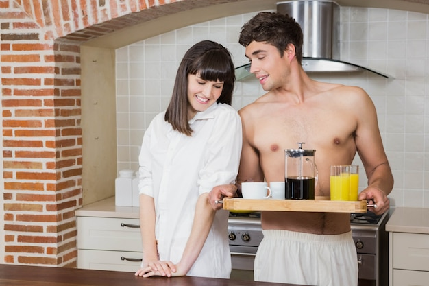 Young couple with breakfast tray in kitchen