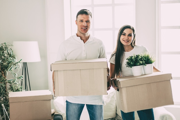 Young couple with cardboard boxes standing in a new apartment