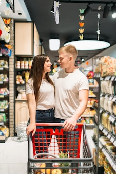 Young couple with cart, confectionery department