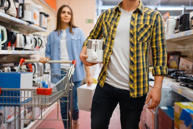 전자 제품 매장에서 장바구니와 젊은 부부. 남자와 여자는 시장에서 가전 제품을 구입