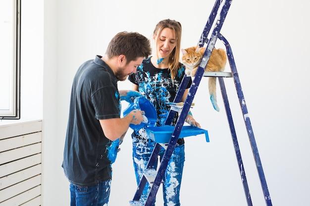 Молодая пара с кошкой делают ремонт в новой квартире.