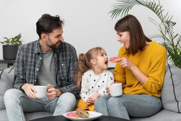 Giovani coppie con il bambino che mangia le ciambelle