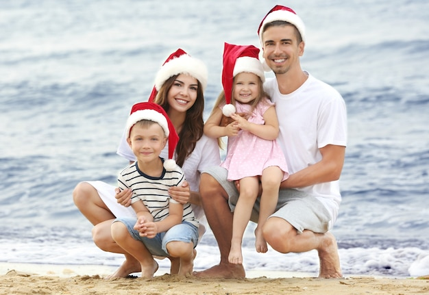 Young couple with children on beach. christmas concept