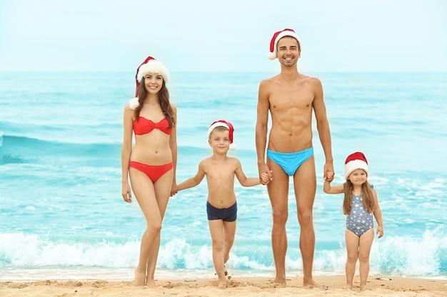 ビーチで子供と若いカップル。クリスマスのコンセプト