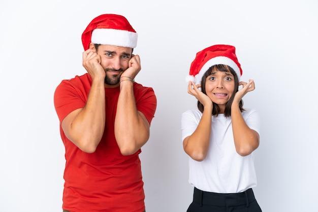 Молодая пара в новогодней шапке на белом фоне, закрывая оба уха руками