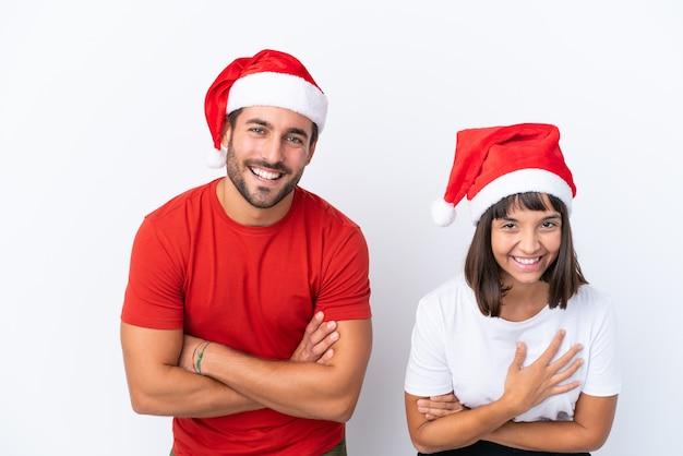 Молодая пара в новогодней шапке на белом фоне, скрестив руки и улыбаясь