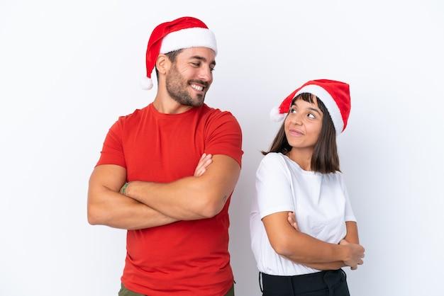 Молодая пара в новогодней шапке на белом фоне, глядя через плечо с улыбкой
