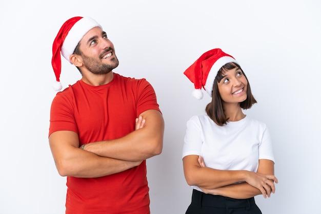 Молодая пара в новогодней шапке, изолированные на белом фоне, глядя вверх, улыбаясь
