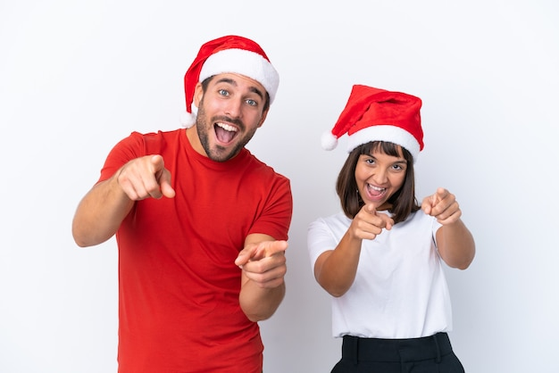 Молодая пара в новогодней шапке на белом фоне указывает пальцем на вас, улыбаясь