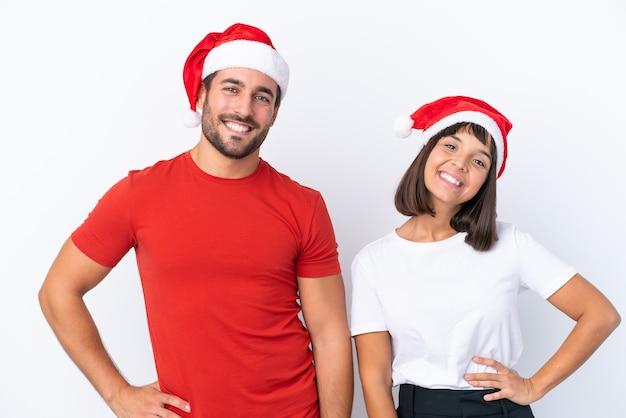 Молодая пара в новогодней шапке, изолированные на белом фоне, позирует с руками на бедрах и улыбается