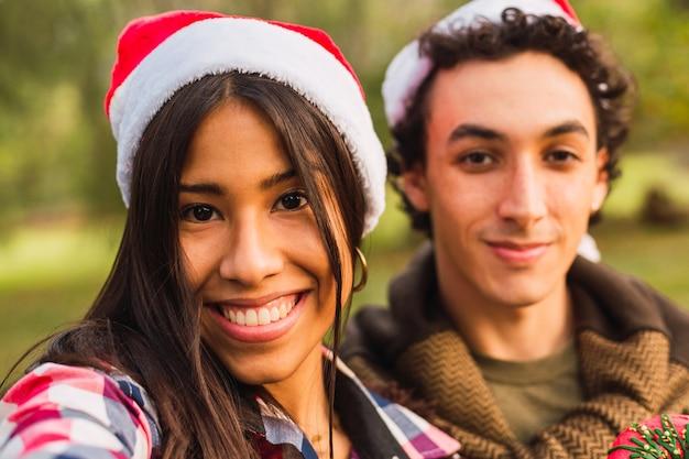 クリスマスの帽子をかぶった若いカップルが自分撮りをします。クリスマスの時期に幸せなカップル。クリスマスと愛の概念。