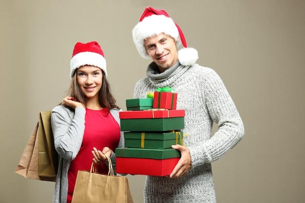 Молодая пара с рождественскими покупками на цветном фоне