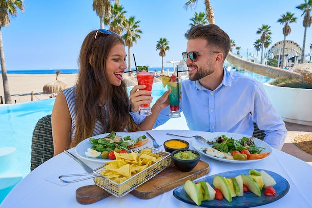 Young couple with cocktails in pool restaurant