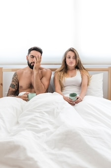 Young couple with cup of coffee sitting on bed