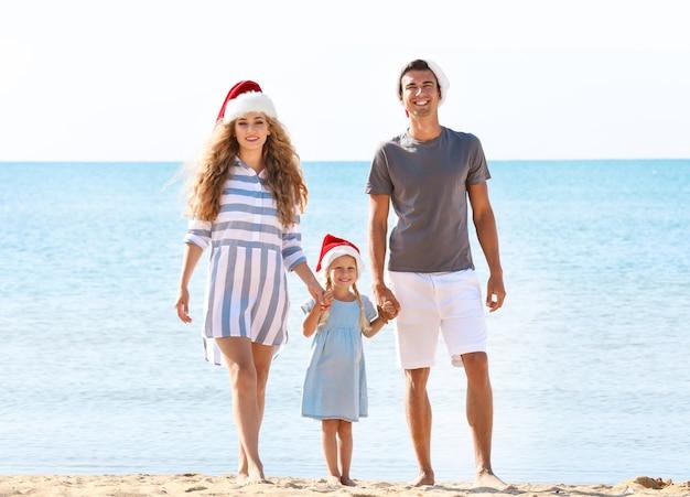 해변에서 귀여운 소녀와 젊은 부부. 크리스마스 축 하 개념