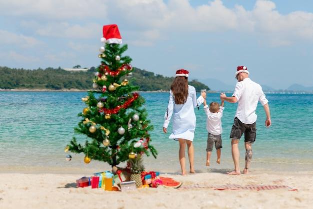 ビーチでかわいい息子と若いカップル。クリスマスのお祝いのコンセプト。