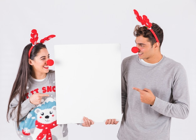 Young couple with deer antlers headbands and funny noses holding tablet