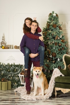A young couple with a dog fooling around near a christmas tree. happy new year and merry christmas