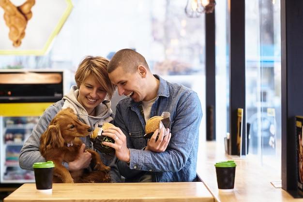 ファーストフードの昼食をとっている犬と若いカップル