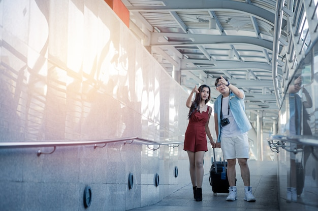 Young couple with dragging a suitcase and talking while to travel in the city.