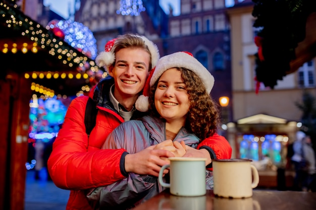 Young couple with drinks on christmas market in wroclaw, poland