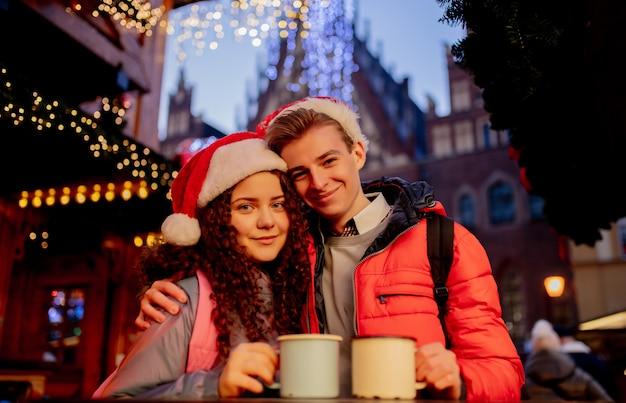 ポーランド、ヴロツワフのクリスマスマーケットで飲み物と若いカップル