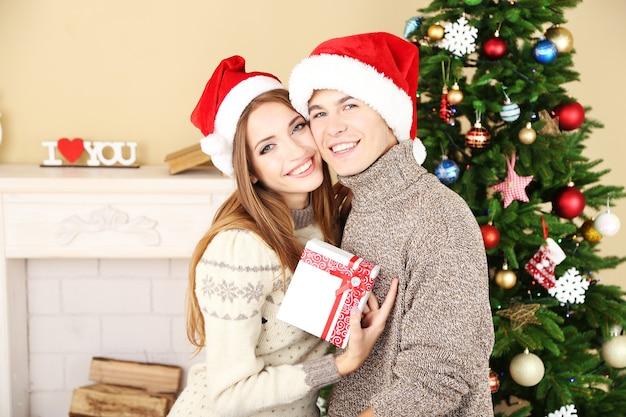 Молодая пара с подарками возле елки