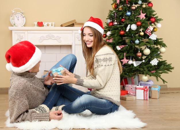 Молодая пара с подарками, сидя на ковре, дома