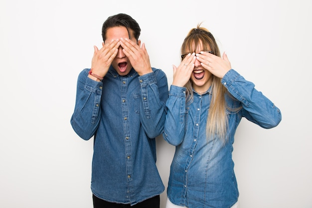 Young couple with glasses covering eyes by hands.