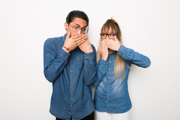Young couple with glasses covering mouth with hands for saying something
