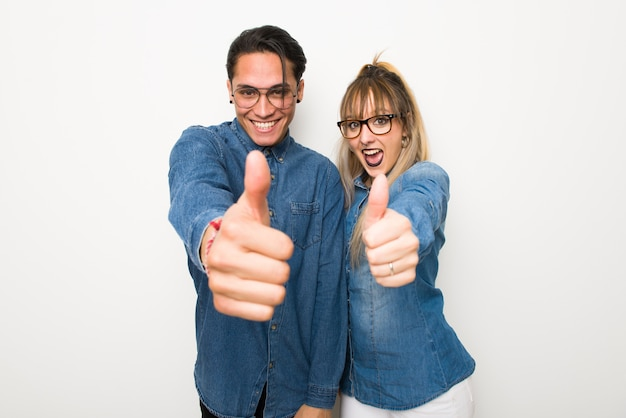 Young couple with glasses giving a thumbs up gesture