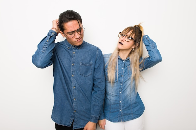 Young couple with glasses having doubts while scratching head