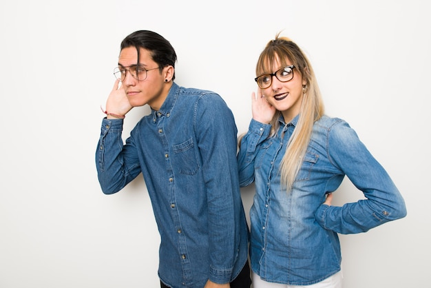 Young couple with glasses listening to something by putting hand on the ear