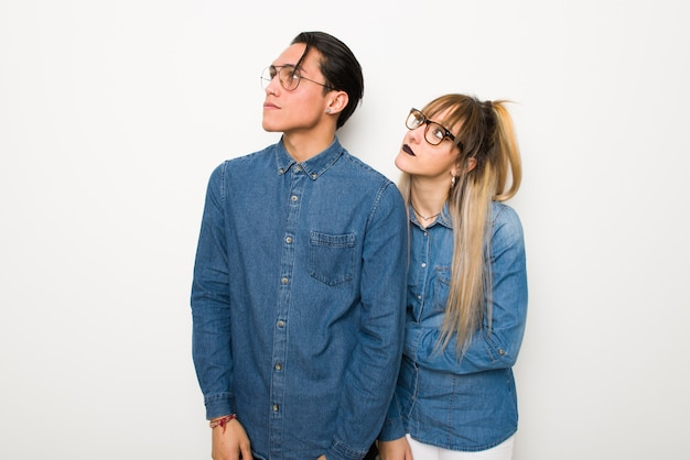 Young couple with glasses looking up with serious face