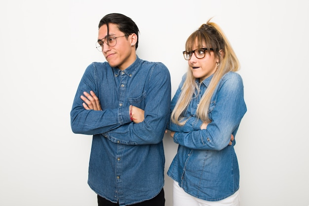 Young couple with glasses making doubts gesture while lifting the shoulders